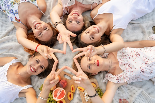 Company of beautiful girlfriends have fun and enjoy a picnic outdoors