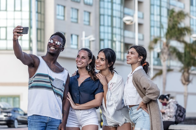 Company of cheerful diverse friends taking selfie in city