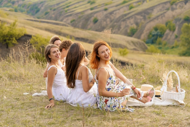 The company of cheerful female friends in white dresses enjoys a view of the green hills, relaxing on a picnic.