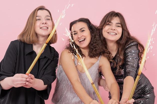 Una compagnia di ragazze allegre con fuochi d'artificio di candele festa di capodanno