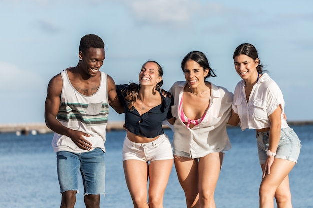 Company of diverse friends hugging at seaside