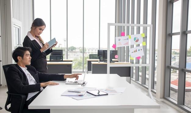 若いエグゼクティブ秘書アシスタント、チームリーダー、または上級マネージャーを指導する企業幹部が後輩に職務を説明する