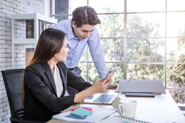 회사 임원인 젊은 아시아 사업가이자 코칭 개인 비서 비서 사업가 파트너는 사무실에서 스마트폰과 전략을 잡고 함께 일하고 있습니다.