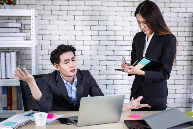 회사 임원인 젊은 아시아 사업가이자 개인 비서 보조 사업가 파트너를 코칭하는 동안 랩톱 컴퓨터와 사무실에서 비즈니스 이익 전략을 함께 작업합니다.