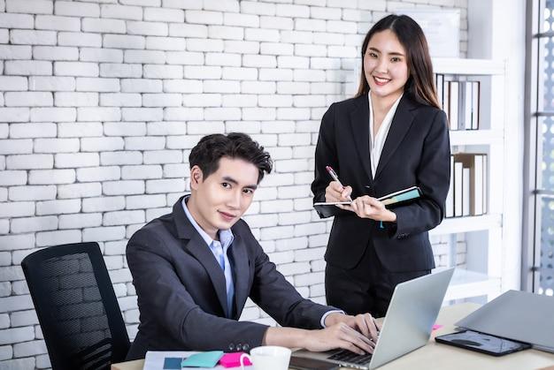 회사 임원 젊은 아시아 사업가와 개인 비서 사업가 파트너가 일하는 동안 사무실에서 비즈니스 이익을 위해 노트북에서 성공적인 비즈니스 계획을 메모하도록 합니다.