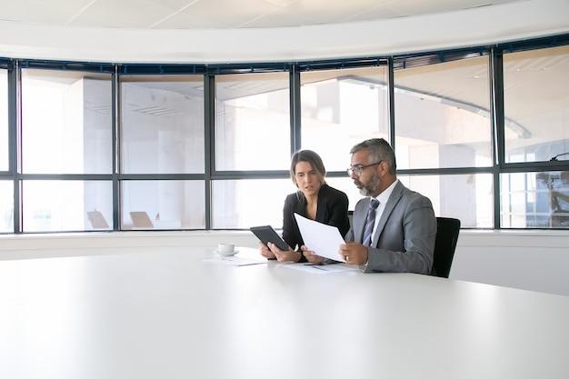 レポートを分析して議論する会社の幹部。一緒に座って、ドキュメントを見て、タブレットを持って話している2人の同僚。ワイドショット。コミュニケーションの概念