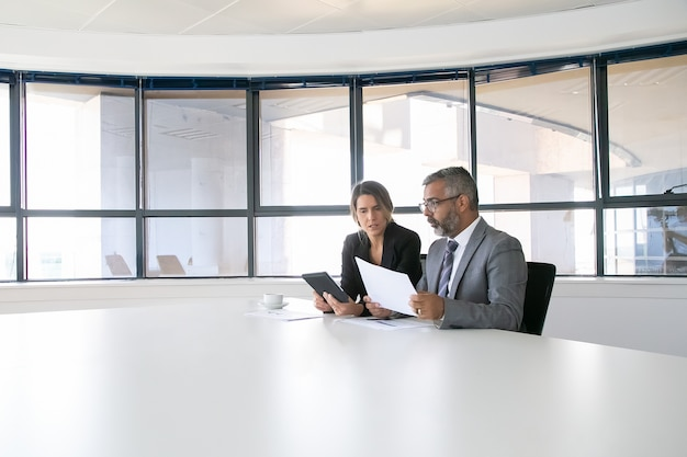 Company executives analyzing and discussing reports. two business colleagues sitting together, looking at document, holding tablet and talking. wide shot. communication concept