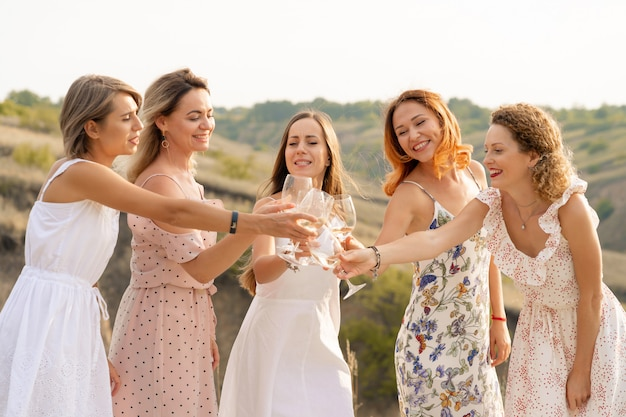 The company of female friends enjoys a summer picnic and raise glasses with wine