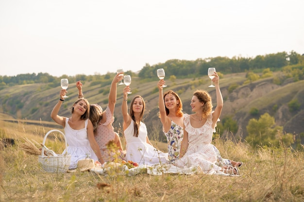 The company of female friends having fun and enjoys a summer green hlls picnic and raise glasses with wine. people concept.