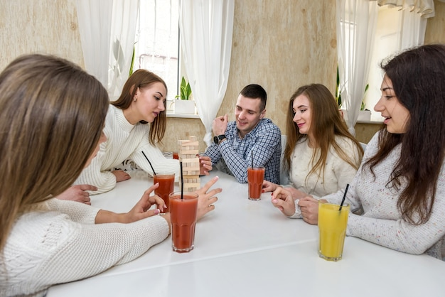 The company of friends drinks juice and playing tower game in the cafe