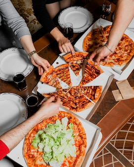 Company of friends eating pizza and talking