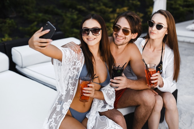 Company of friends taking selfies on the beach