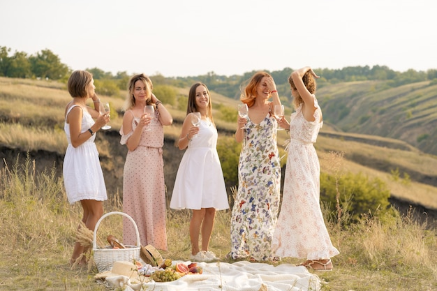 Company of gorgeous female friends having fun and enjoys a summer green hlls picnic, dancing and drink alcohol. people concept.