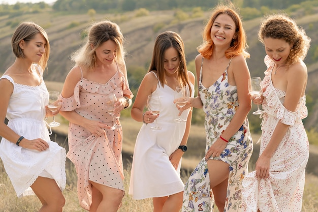 The company of gorgeous female friends having fun and enjoys a summer green hlls picnic, dancing and drink alcohol. people concept.