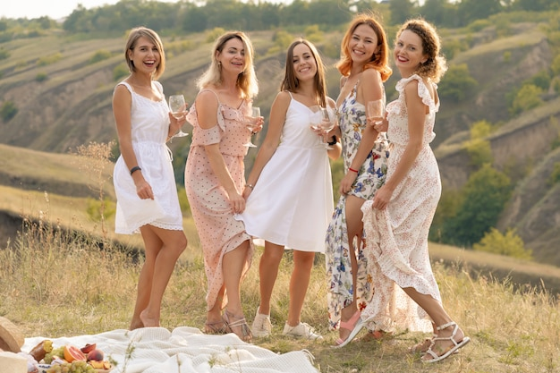 The company of gorgeous female friends having fun and enjoys a summer green hlls picnic