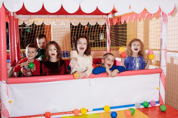 Company of happy children in the pool with colored balls. children's party.