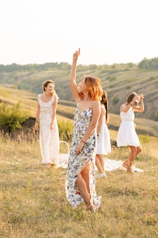 The company of happy female friends having fun and dancing outside in a picnic at hills.