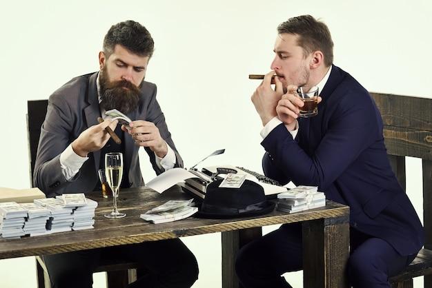 불법 사업에 회사 돈 더미와 함께 테이블에 앉아 남자 불법 사업 개념 음주와 흡연 동안 불법 거래를 논의하는 기업인