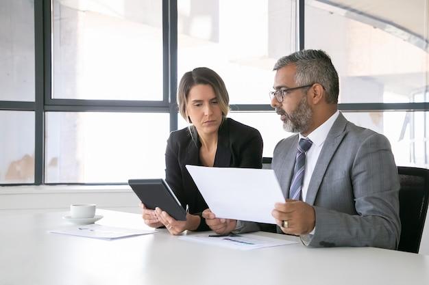 レポートを分析する会社のリーダー。一緒に座って、ドキュメントを見て、タブレットを持って話している2人の同僚。ミディアムショット。コミュニケーションの概念