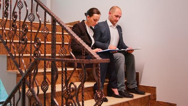 階段に座って残業をしている会社のマネージャーは、締め切りが難しい同僚を助けています。同僚の起業家が夕方、階段に座って企業の仕事で一緒に働いて、プロジェクトを説明します。