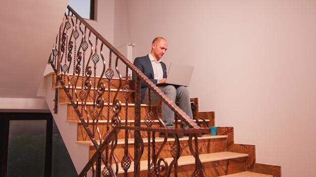 財務ビルの階段に座って締め切りにラップトップの過労を使用している会社のマネージャー。現代の金融職場で働く階段のビジネスマンの仕事で残業をしている事務局長。