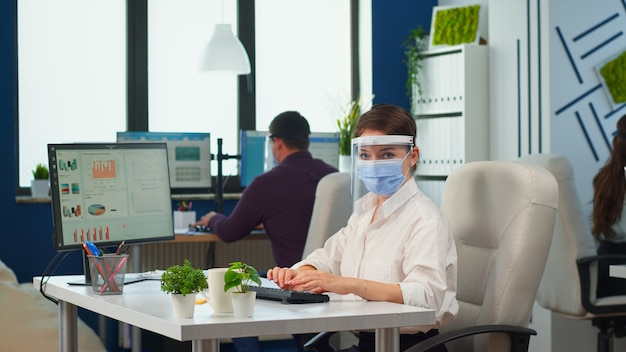 Company manager with face mask typing on computer and looking on camera in new normal business office respecting social distance during coronavirus pandemic. colleagues working in background.