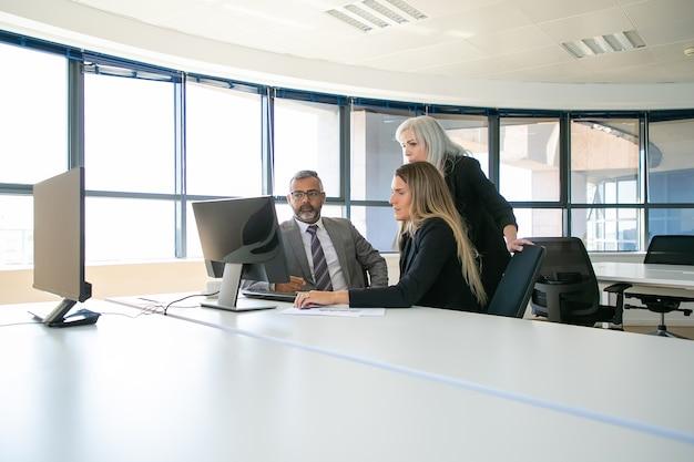 Менеджеры компании обсуждают решение. бизнесмены собираются в конференц-зале, вместе смотрят контент на мониторе компьютера. деловое общение или концепция совместной работы