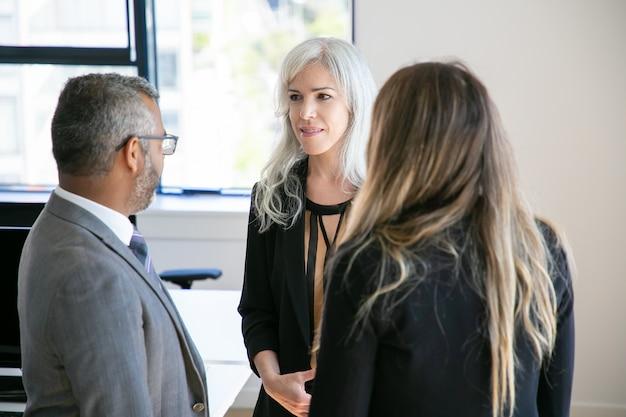 Менеджеры компаний в костюмах, стоя в офисе, разговаривают, обсуждают проект. средний план. деловое общение или концепция брифинга