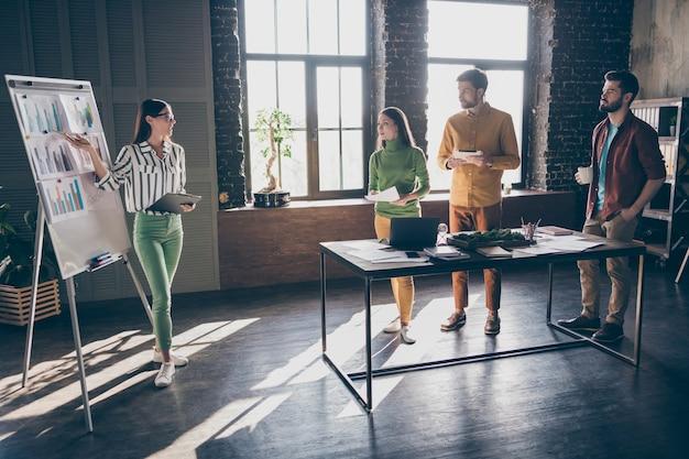 Компания из четырех симпатичных привлекательных умных умных трудолюбивых людей-спикеров демонстрирует план диаграммы доходов и доходов на рабочем месте в офисе станции в помещении