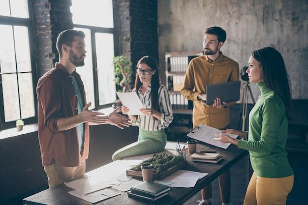 4人の素敵な焦点を絞った忙しい熟練した資格のあるビジネスマンの会社