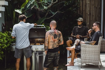 Company of friends cooking barbecue grill outdoors
