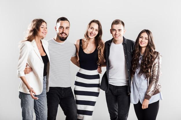 세련된 캐주얼 옷을 입은 친구들이 스튜디오의 흰색 배경에 함께 서서 미소를 짓고 있습니다.