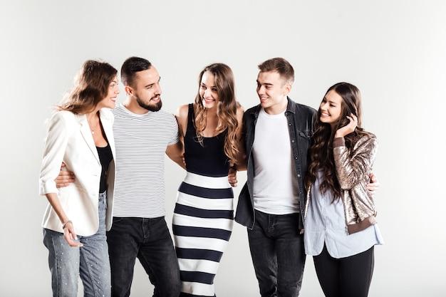 세련된 캐주얼 옷을 입은 소녀들과 남성들이 스튜디오의 흰색 배경에 대해 이야기합니다.