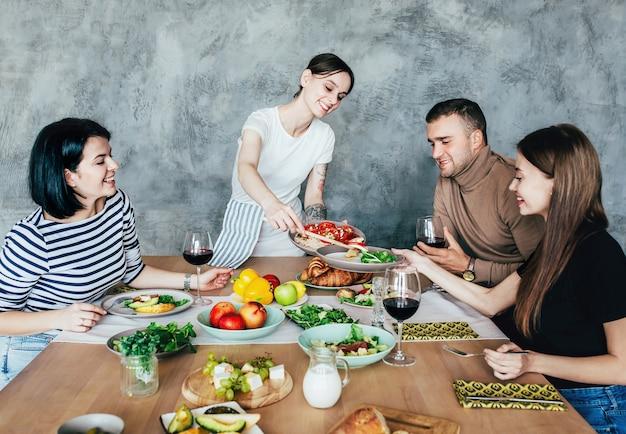 楽しんでおしゃべりを楽しんでいる飲み物や食べ物とセットのテーブルで自宅で男性と女性の会社