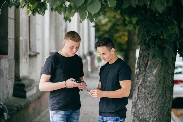 町で歩くスマートフォンを持つ若い友人の会社