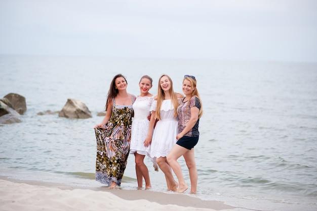 Компания молодых девушек, идущих по морю