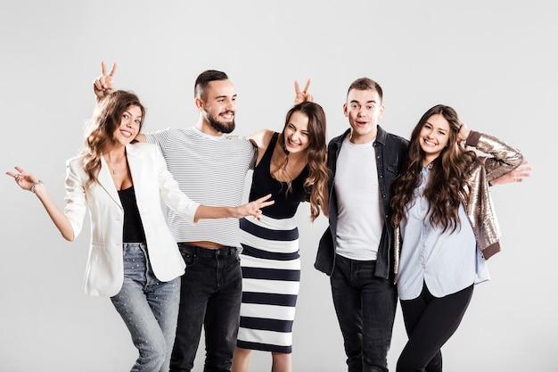 세련된 캐주얼 옷을 입은 젊은이들의 회사는 스튜디오의 흰색 배경에서 함께 웃고 즐겁게 지냅니다.