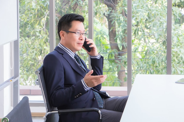 The company's top executives are asian businessmen, thai people are talking on the phone in the meeting room, enjoying the country with a smiling face and a confident look.