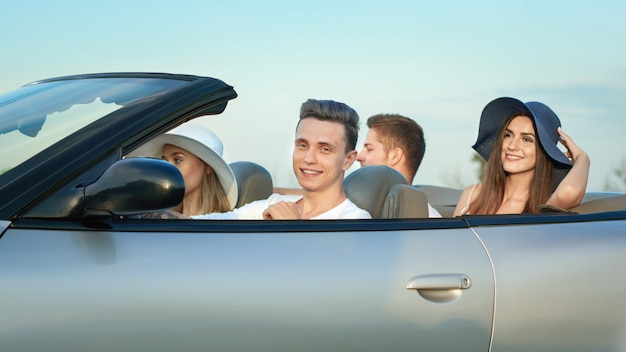 Company sitting in cabriolet, traveling by car.