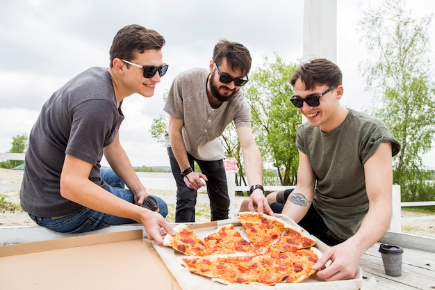 Company of smiling friends eating pizza on picnic