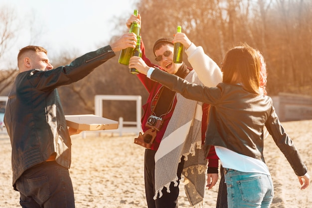 Company of smiling friends having fun with beer in open air