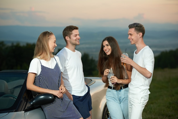 Company standing near cabriolet, smiling and communicating.