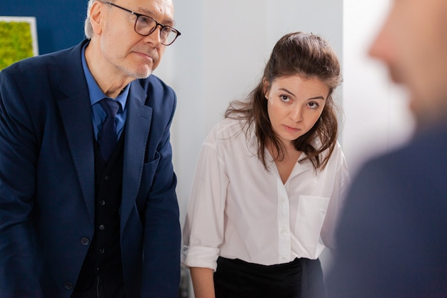 シニアビジネスオーナーの計画協力と協力する会社の戦略アドバイザー。オフィスで議論する成功の財務戦略を計画している多民族の同僚。