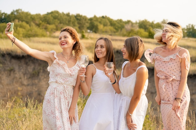 The company of stylish happy female friends having fun and making selfie with vine glasses outside