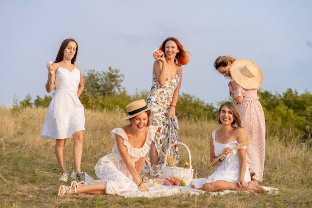 The company of stylish happy female friends having fun on outdoor retro style picnic party