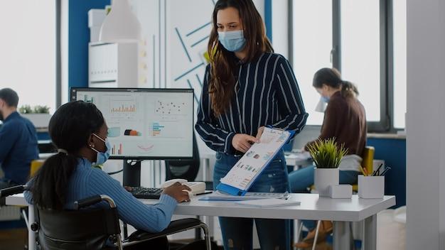 保護フェイスマスクを着用して財務グラフィックをチェックする会社のチーム