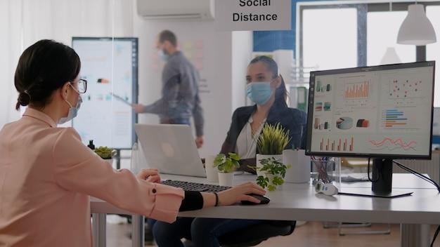 Covid19の感染を防ぐために保護フェイスマスクを着用して、営業所のコンピューターで作業しながら財務グラフィックを確認している会社のチーム。社会的距離を尊重するチーム