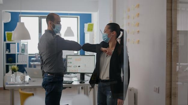 コロナウイルス感染を防ぐために肘に触れる医療用フェイスマスクを備えた会社のチーム。新しい通常のオフィスで働いている間。 covid19世界的大流行の際の社会的距離を尊重する同僚