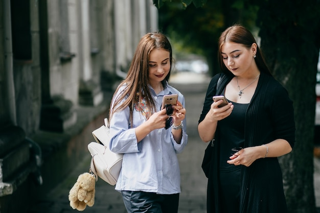 Company of young friends with smartphones walking in city