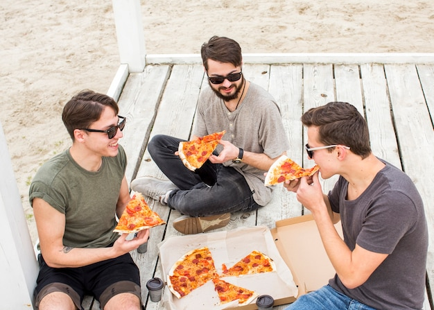 Company of young guys eating pizza on beach